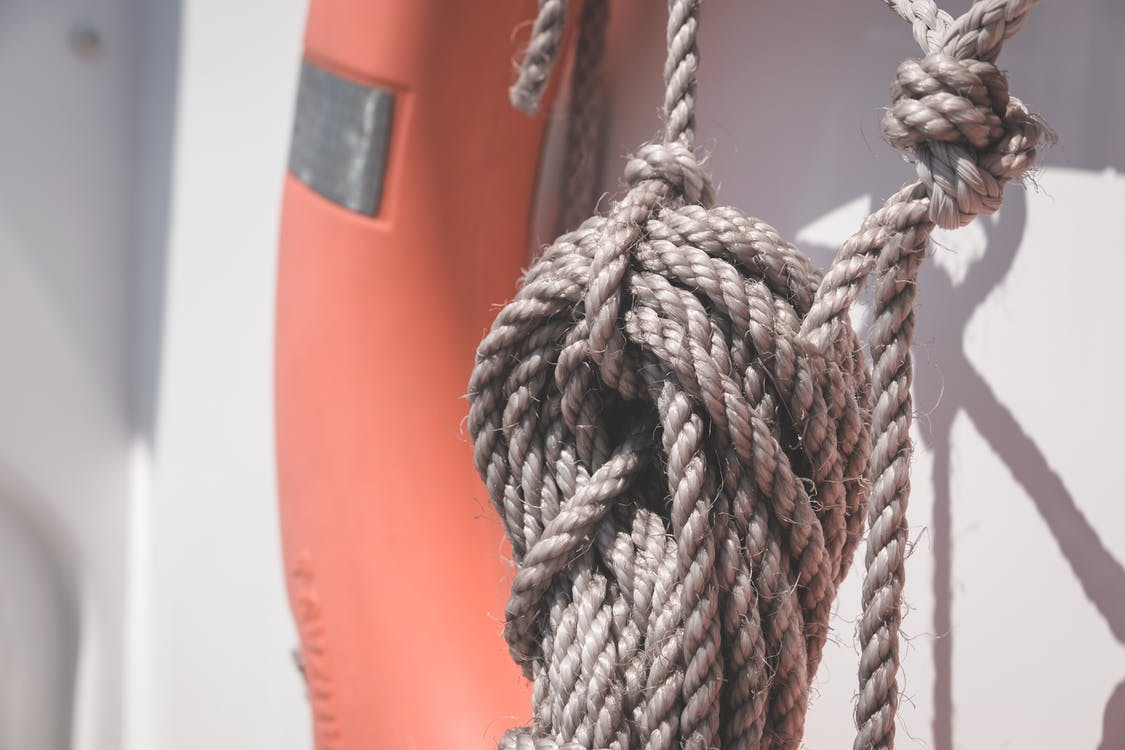 Tangled rope hanging on yacht in sunlight