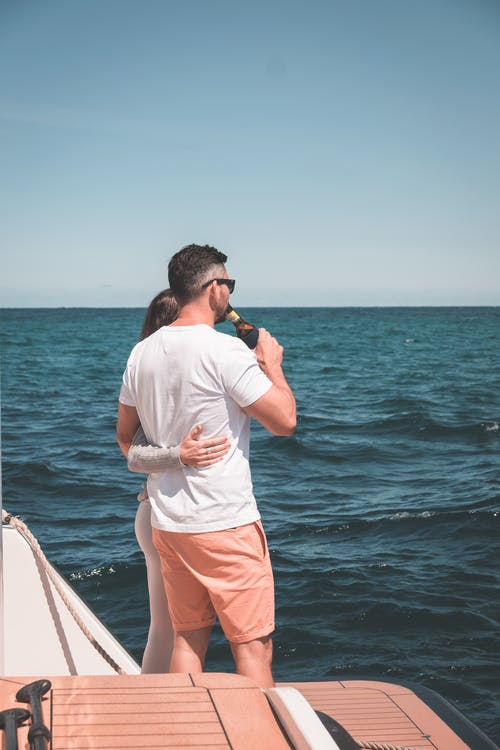 Side view of unrecognizable young couple in casual clothes embracing and drinking beer while admiring sea during cruise on yacht against cloudless blue sky