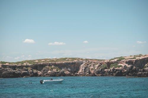Boat floating on sea near rocky island under blue sky