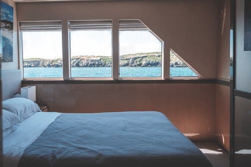 Interior of cabin in modern yacht with comfortable bed and windows overlooking picturesque sea and rocky cliff on sunny day