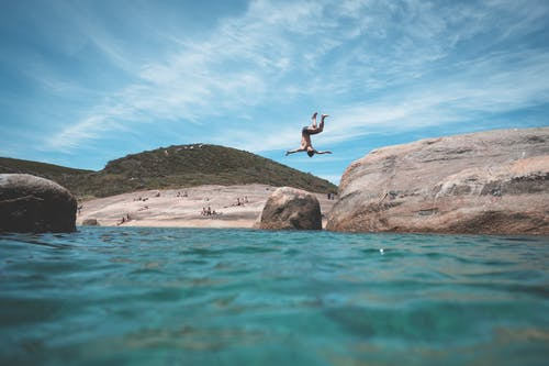 Anonymous man jumping into ocean during summer vacation