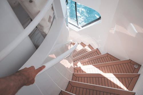Anonymous man walking downstairs in modern boat during cruise