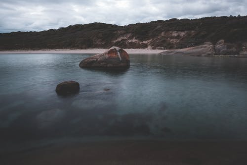 Picturesque landscape of rocky boulders in calm ocean water near sandy beach surrounded by hills covered with lush green trees against cloudy sky