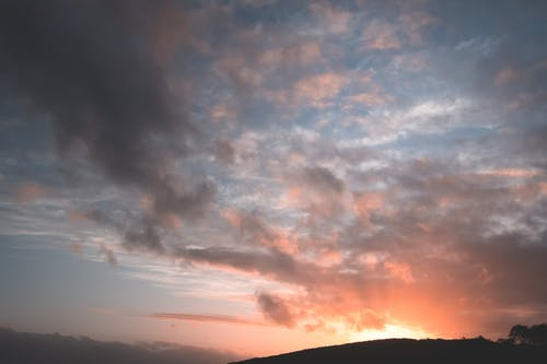 From below of colorful fluffy clouds floating in picturesque sunset sky over mountainous valley