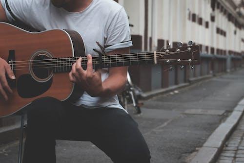 Crop guitarist playing on street