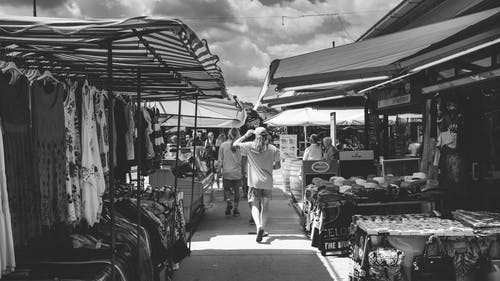 Black and white of crowd of people strolling in market with different clothes and goods in daytime