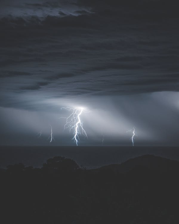 Shiny dangerous majestic lightnings with thunder in cloudy sky over water of ocean at night