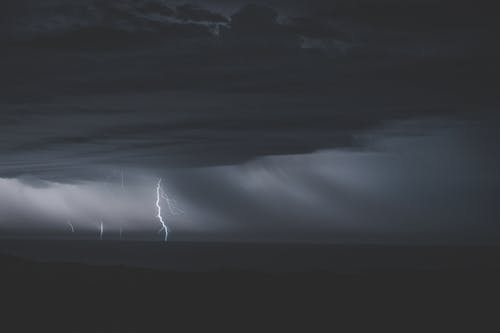 Cloudy rainy sky with shiny bright lightning in stormy ocean at late night