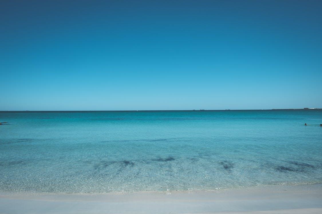 Peaceful azure sea under cloudless bright blue sky