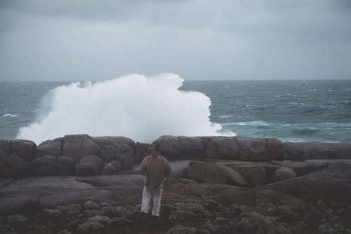 Person standing on rocky coast and looking at stormy sea