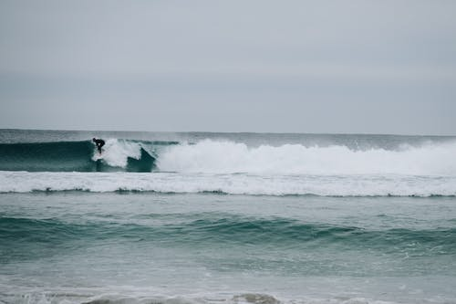 Anonymous surfer riding surfboard on foamy waves of powerful stormy sea in cloudy day
