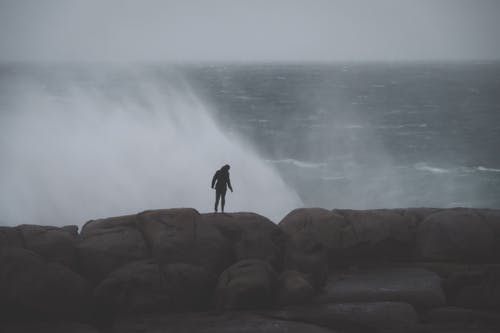 Back view of unrecognizable male standing on rocky cliff and admiring stormy sea with splashes in cloudy day