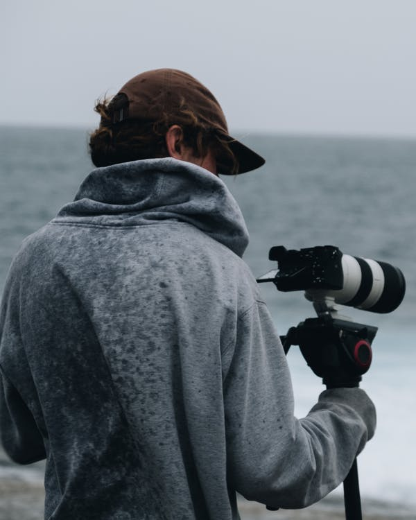 Photographer shooting on photo camera near ocean in cloudy day