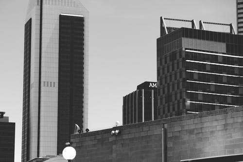 Black and white exteriors of different modern buildings located in commercial district of city against cloudy sky