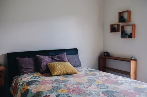 Cozy bed with colorful pillow and coverlet in light bedroom