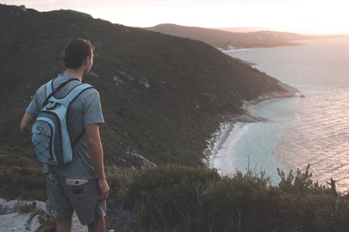 Unrecognizable male hiker enjoying seascape from grassy hilltop at sundown