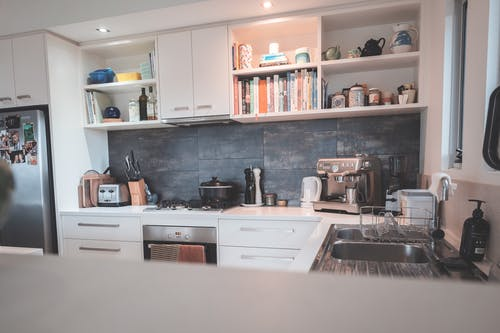 Kitchen with minimalist furniture and modern appliances in flat