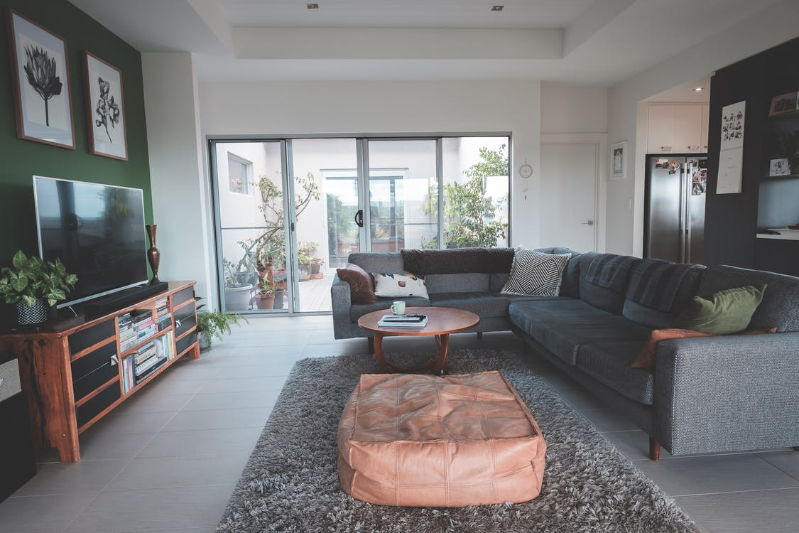 Interior of spacious living room with round coffee table placed on soft rug near comfortable sofa ad modern TV in cozy villa
