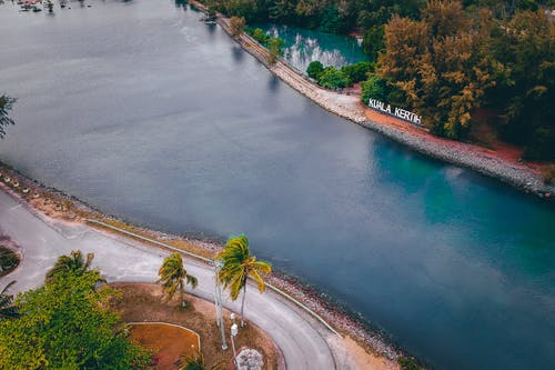 Aerial view of wide river flowing near narrow asphalt road and lush green trees