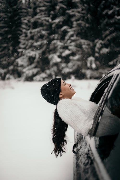 Side view of cheerful female with long hair wearing warm hat and sweater enjoying snowfall from car window in woods