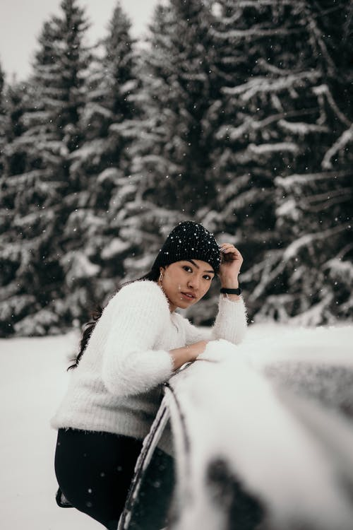 Side view of ethnic female in warm sweater and hat sitting on car in winter woods and looking at camera