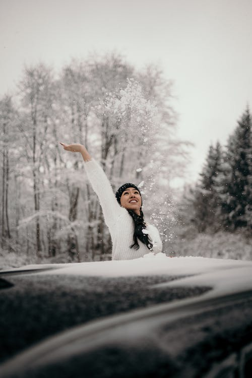 Carefree ethnic female throwing up snow near car