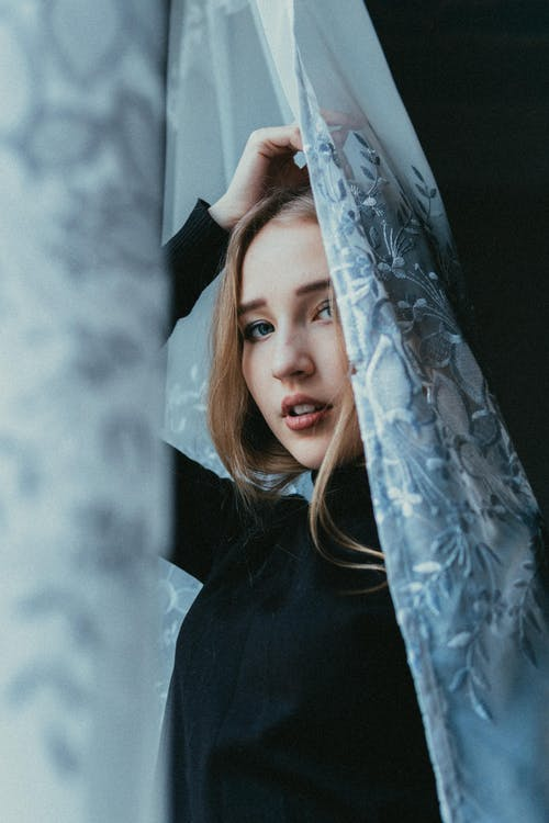 Low angle of sensual young female standing behind curtain and looking at camera
