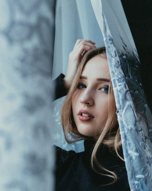 Sensual woman behind curtains near window