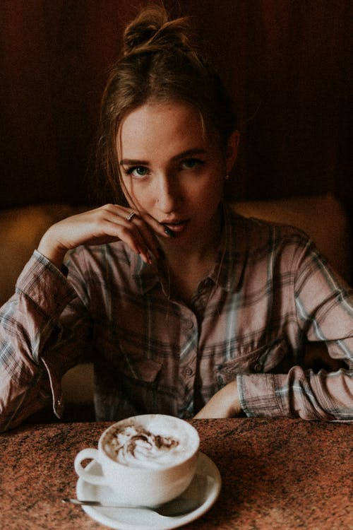 High angle of serious female touching face sitting at table with cappuccino with froth in coffee shop
