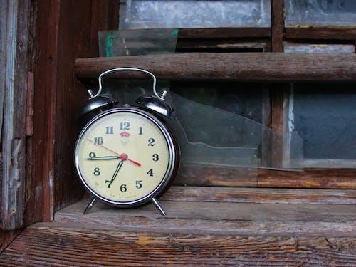 An Alarm Clock on Wooden Shelf