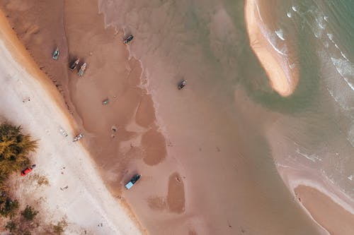 Drone view of wavy pure sea water washing sandy coast with boats and green trees