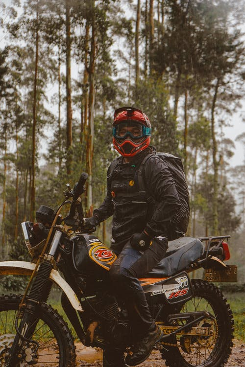 Side view of male biker in protective helmet with backpack sitting on motorcycle in woods