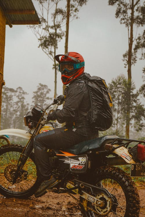 Male motorcyclist in helmet riding in forest