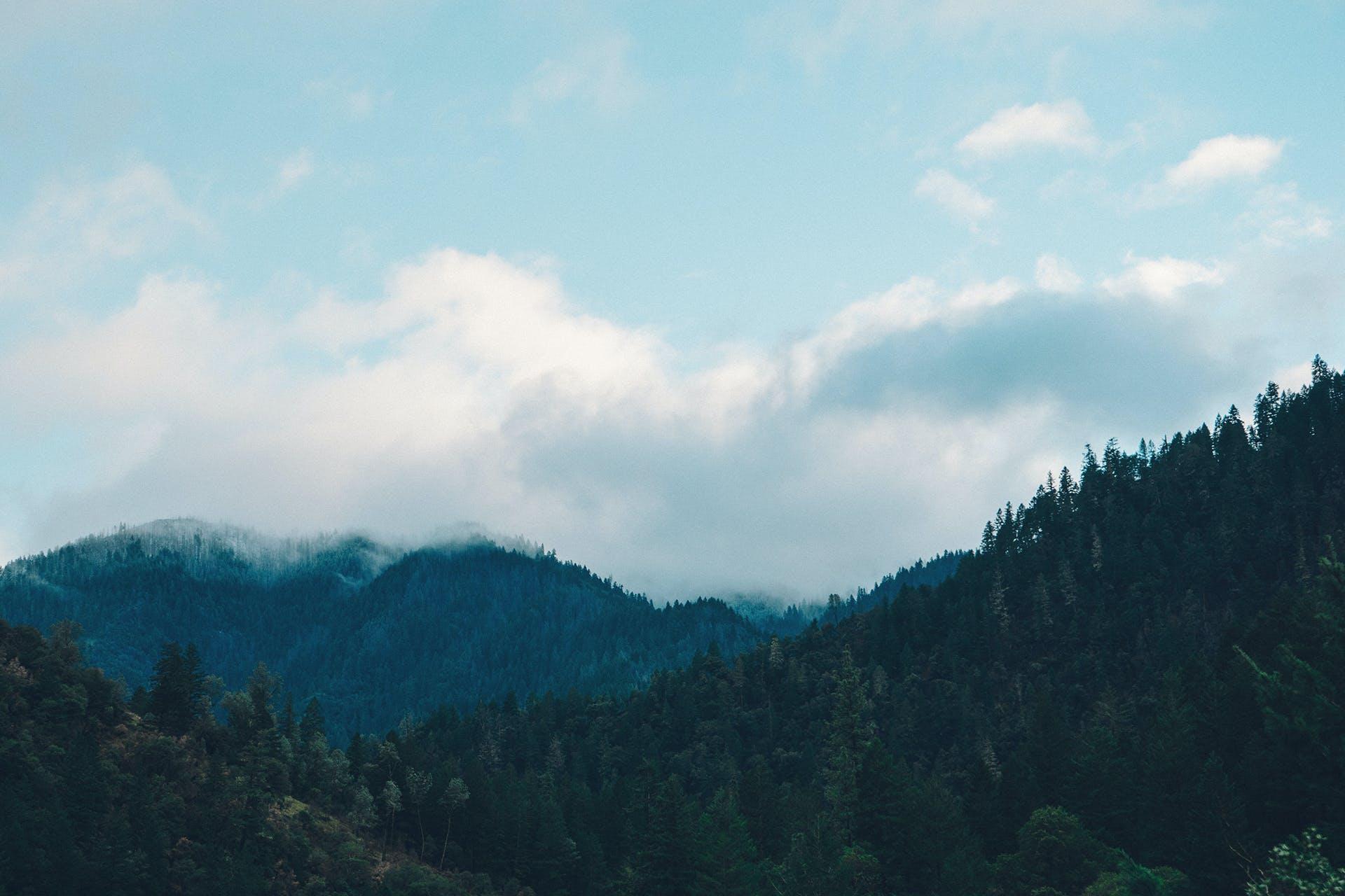 Mountain Range Under White Clouds