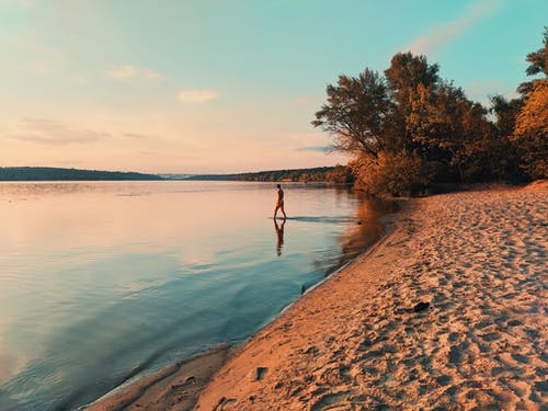 Woman in swimwear in water of lake at sunset