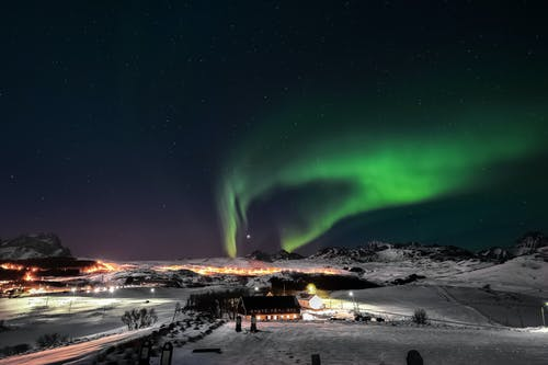 People Walking on Snow Covered Ground Under Green Sky during Night Time
