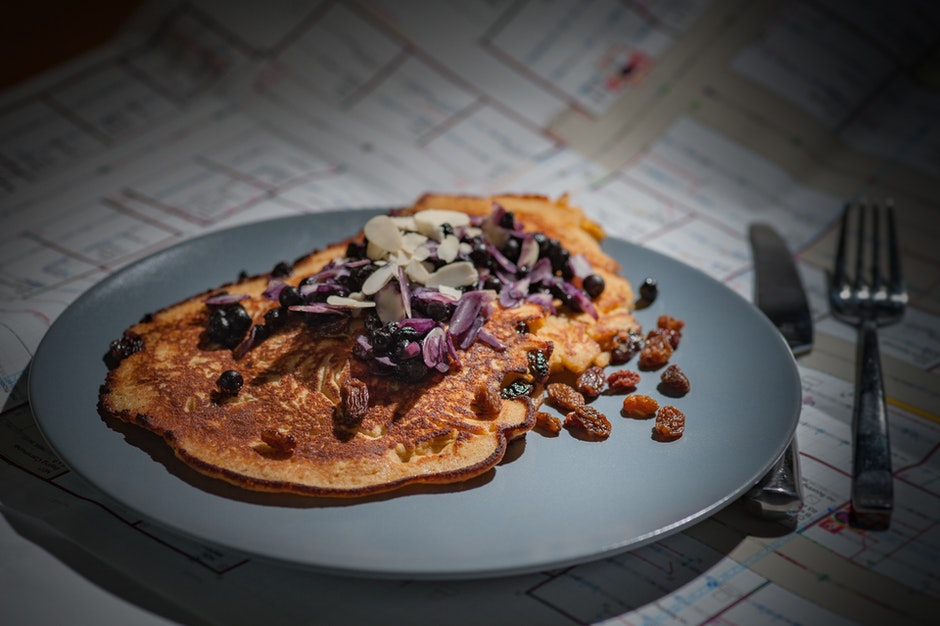 Brown Pancake With Brown Purple White Nut on Grey Round Plate Beside Silver Knife and Fork