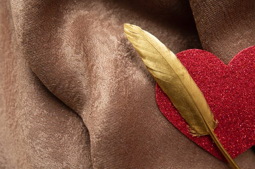 Top view of shiny decorative red heart with long golden feather placed on soft brown plaid during festive event celebration
