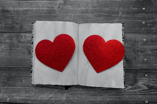 Top view of decorative red paper hearts on white pages of notepad placed on wooden surface during Saint Valentine day