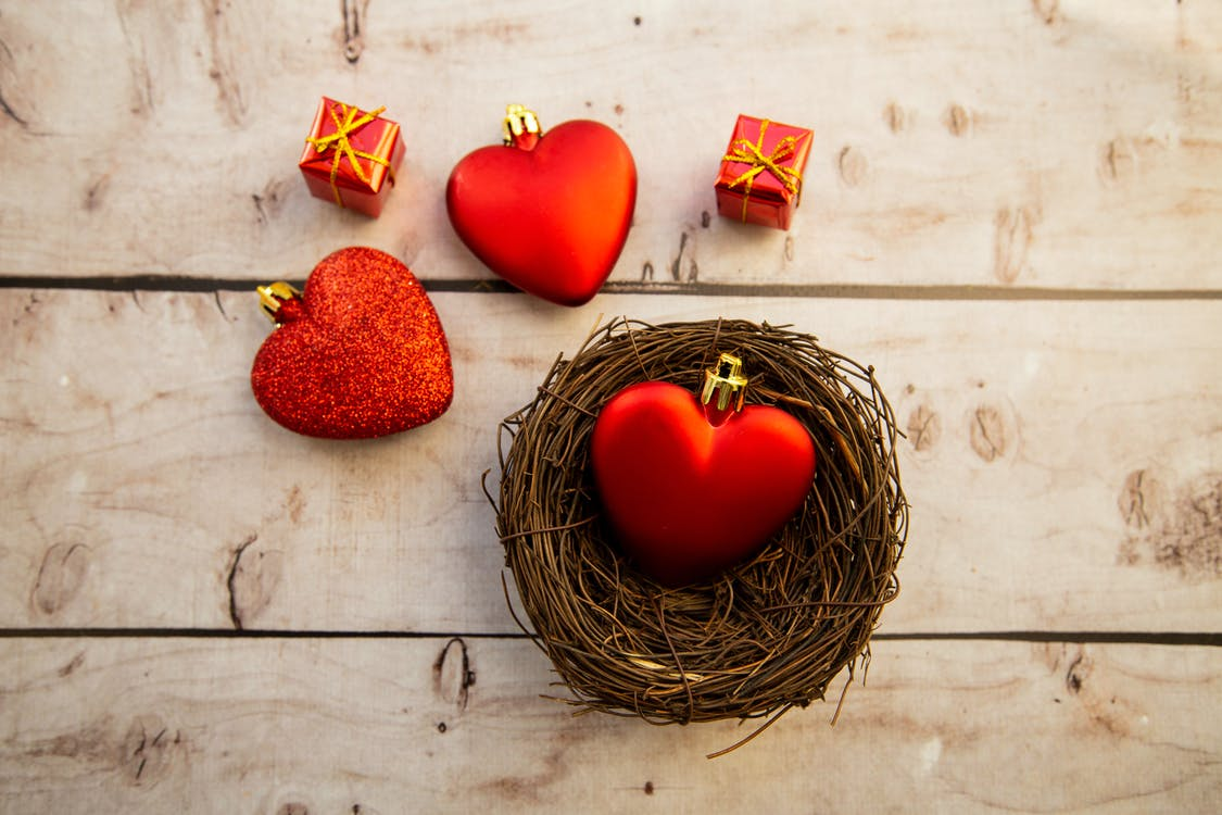 Top view of heart shaped decorations with small decorative gift boxes placed on wooden surface with wicker bowl during Saint Valentine day