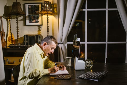 Side view of concentrated mature male accountant in shirt taking notes in planner while sitting at table in classic styled apartment and working remotely using calculator and tablet
