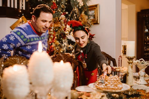 Happy adult multiethnic couple serving table while standing near decorated fir tree during Christmas celebration at home