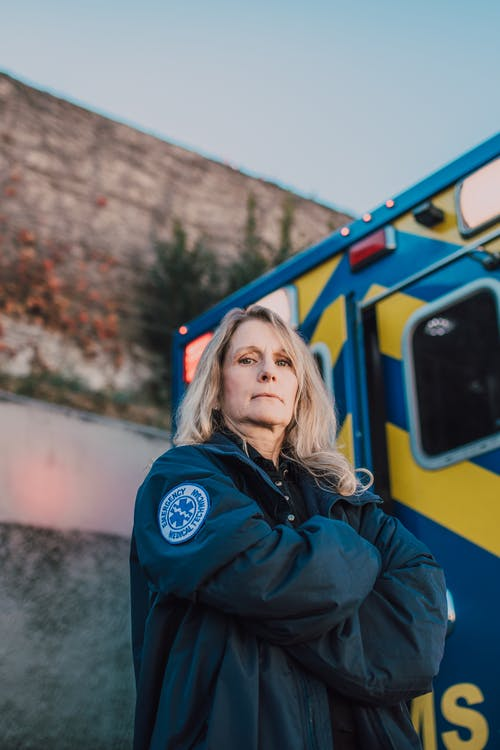 Woman in Blue Jacket Standing Beside Blue and Yellow Ambulance