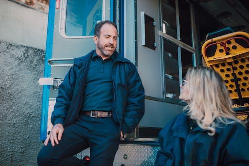 Man in Blue Jacket Standing Beside a Woman