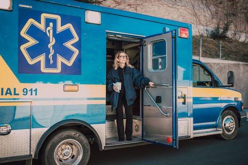 Paramedic Holding on Ambulance Door
