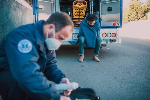 Man Sitting at the Back of an Ambulance