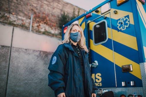 Woman Wearing a Mask Standing Behind an Ambulance