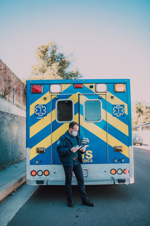 Paramedic Standing Behind an Ambulance