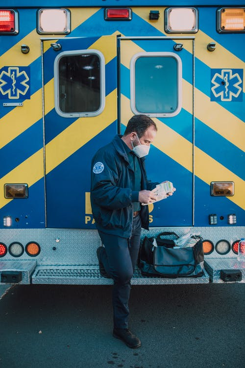 Paramedic Wearing a Mask Standing Behind an Ambulance