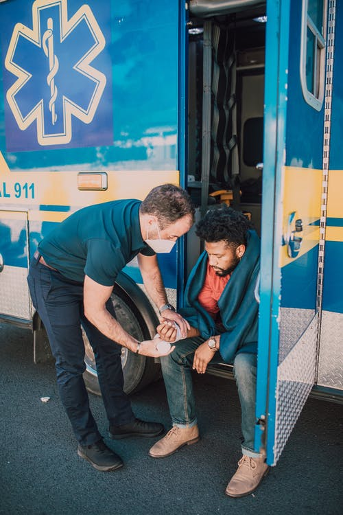 EMT Wrapping Bandage on Man's Arm